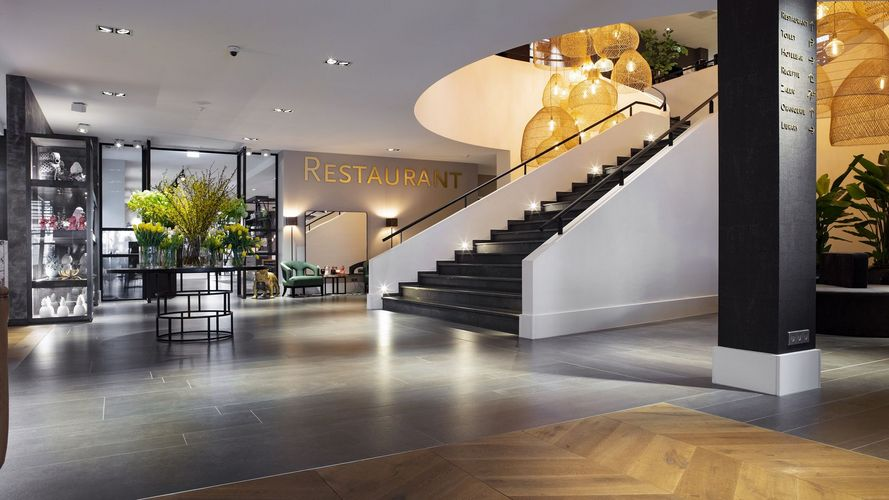The spacious entrance area with a view of the stairs and the restaurant entrance